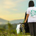 dziewczyna pchająca wózek inwalidzki